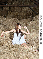 Woman in white dress on haystack