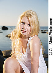 Woman in white dress on seashore background
