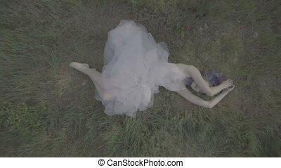 Woman in white dress on the grass.