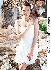 Woman in white dress on tropical beach near palm trees.