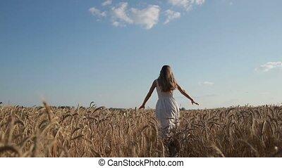 Woman in white dress running through wheat field