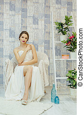 Woman in white dress sitting on armchair.