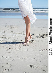 Woman in white dress stepping on the beach on a bright day