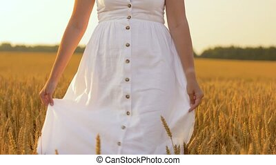 woman in white dress walking along cereal field -...
