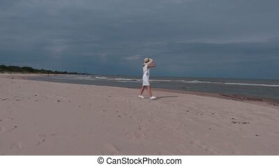 Woman in white dress walking near sea