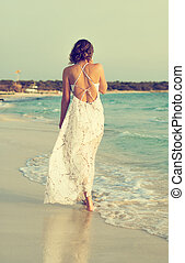Woman in white dress walking on the beach.