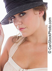 Woman in white holding black hat