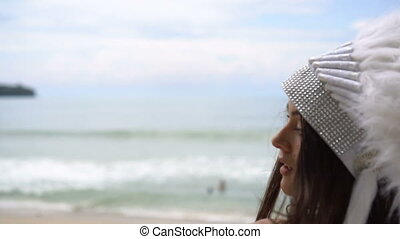Woman in white indian feather hat at the beach