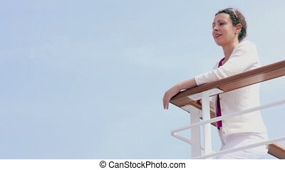 Woman in white jacket stands at fence corner during cruise
