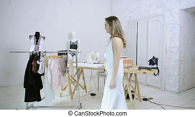 Woman in white nightie comes to rack with hangers to choose clothes