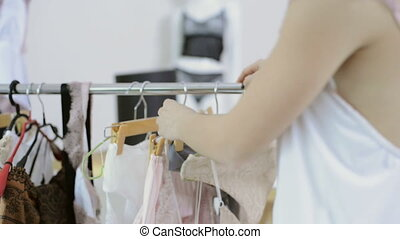 Woman in white nightie comes to rack with hangers choose transperent