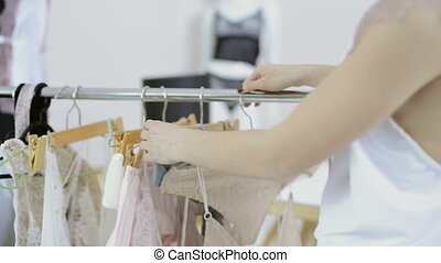 Woman in white nightie comes to rack with hangers to choose underwear
