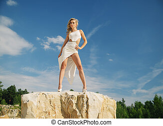 Woman in white posing on the rocks