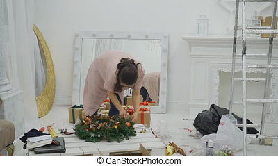 Woman in white room is working on decorating a Christmas...