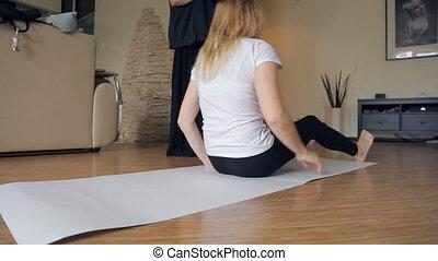 Woman in white shirt, black leggings lies on large sheet of paper.