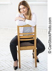 Woman in white sit backwards on chair