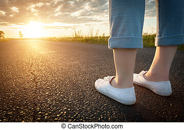 Woman in white sneakers standing on asphalt road towards sun. Travel, freedom concepts.