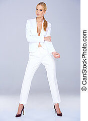 Woman in white suit standing confidently