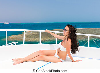 Woman in white swimsuit lying on the deck of the yacht at a sunny summer day
