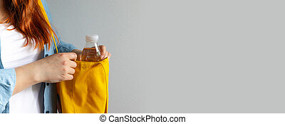 Woman in white T-shirt takes out plastic bottle of water from yellow bag on a gray background with copyspace