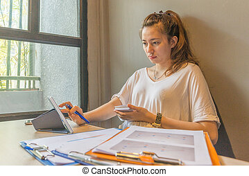 Woman in white T-shirt using tablet next to documents
