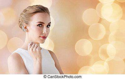 woman in white with jewelry over holidays lights
