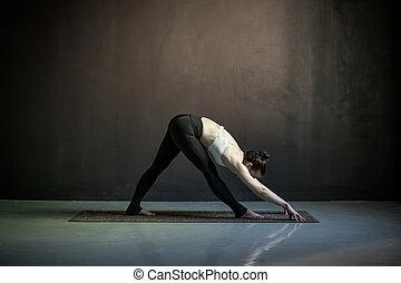 beautiful yoga woman standing in widelegged forward bend