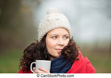 Woman In Winter Clothes Looking Away While Holding Coffee Mug