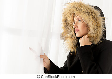 Woman In Winter Clothes Looking Out The Window