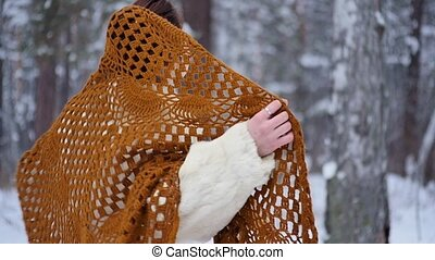 Woman in winter clothes rejoices in warm winter in a snowy forest.