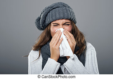 Woman in winter clothes sneezing