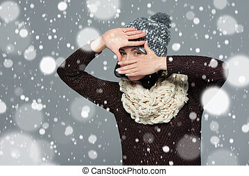 Woman in winter clothing making a frame with her hands
