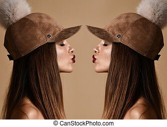 Woman in winter suede pompon hat cap double art composition with closed eyes kissing