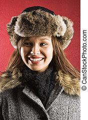 Young adult Caucasian woman wearing fur hat looking to side and smiling.