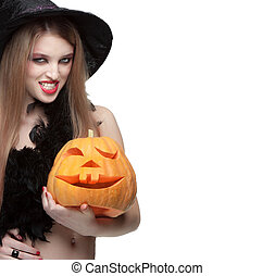Woman in witch costume opens carved Halloween pumpkin and...