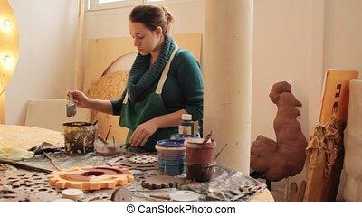 Woman in workshop creating at desktop - Woman in apron...