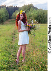 Woman in wreath with bunch of flowers on meadow at summer day
