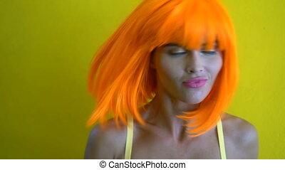 Woman in yellow bra and orange wig - Closeup portrait of...