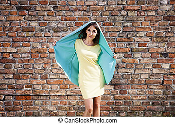 Woman in yellow dress against brick wall