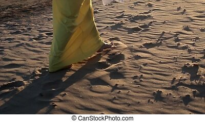 Woman in yellow dress walking on a beach