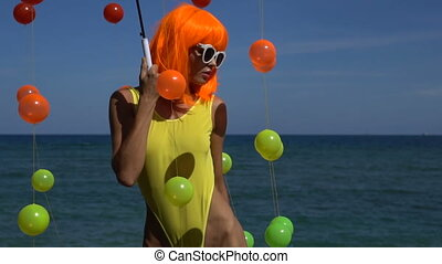 Woman in yellow swimsuit and orange wig - Closeup of sexy...