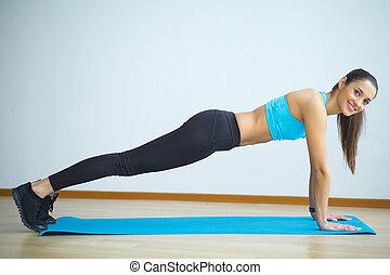 woman in yoga class making upwardfacing dog pose
