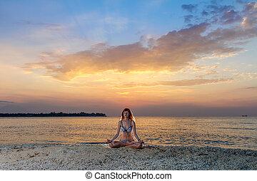 Woman in yoga lotus meditation at sunset