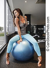 Woman in yoga pants sitting on a bouncy ball