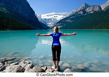 Woman in yoga pose meditating by water.