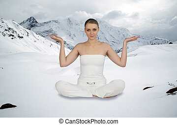 Woman in yoga position sat in front of mountain range