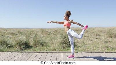 Young woman doing yoga is sunny day in the Tarifa beach, Cadiz, Spain. Horizontal outdoors shot.