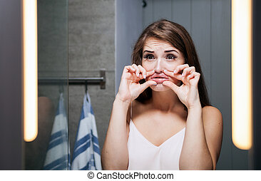 Woman increases her lips in front of a bathroom mirror