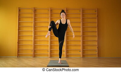 Woman indoors in yellow class space doing stretching legs in...