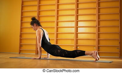 Woman indoors in yellow class space doing stretching legs....